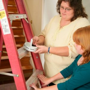 Woman adding batteries to a smoke detector